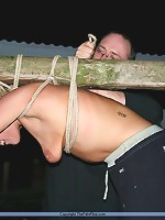 Blonde slave gets tied up to a stick with an onion on her mouth